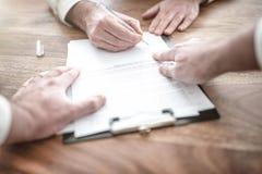 Unterzeichnender Vertrag des Mannes am hölzernen Schreibtisch mit anderer Person, die auf Dokument zeigt stockfoto