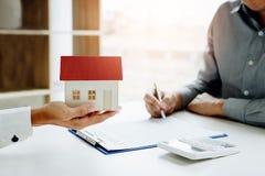 Unterzeichnender Vertrag des neuen Hauskäufers mit Mitteln halten den Modus lizenzfreies stockfoto