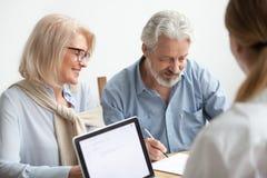 Unterzeichnendes Dokument der glücklichen älteren Paare bei der Sitzung mit Finanza stockfoto