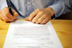 Unterzeichnendes Dokument des Geschäftsmannes am Schreibtisch lizenzfreies stockbild