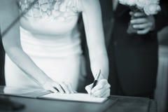 Unterzeichnendes Ehestandsregister der Hochzeitsbraut Stockbilder