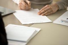 Unterzeichnendes Lastenheft des führenden Vertreters der Wirtschaft am Schreibtisch Lizenzfreies Stockbild