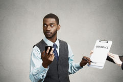 Unterzeichnendes Lastenheft des leitenden Angestellten, das intelligentes Phon hält Stockbild