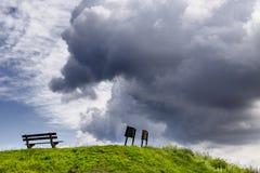 Wolken mit Zeichen und einer Bank Lizenzfreie Stockfotografie