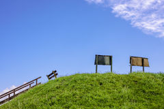 Blauer Himmel mit Zeichen und einer Bank Lizenzfreie Stockfotos