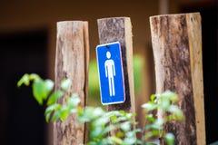 Unterzeichnet das Mannsymbol, das am Holz hängt Lizenzfreies Stockfoto