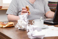 Untidy desk and a thick man with food in his hands Royalty Free Stock Photos