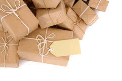 Border pile of brown paper wrapped parcels, one with blank label, isolated on white Royalty Free Stock Photography