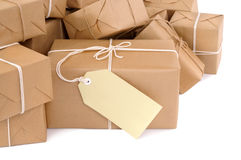 Group of brown paper packages, isolated on white, one with blank label or gift tag Royalty Free Stock Images