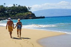 Untill forever. Older couple walks along the beach in Hawaii Stock Photography
