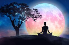 Mountain girl silhouette, meditation under stars, full pink moon. Woman silhouette in yoga lotus pose practicing meditation, contemplating to the stars, on a