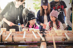 Untitled tourists clean their hands and mouths. KYOTO, JAPAN -OCTOBER 08, 2016: Untitled tourists clean their hands and mouths by holy water before entering Royalty Free Stock Images