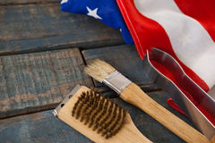Unto spazzola e delle tenaglie con la bandiera americana sulla tavola di legno immagini stock