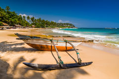 Untouched tropical beach with palms and fishing boats Royalty Free Stock Photos