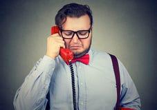 Untröstlicher trauriger Mann, der am Telefon spricht und das unglückliche Gefühl verwüstet schaut stockbild