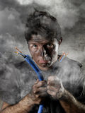 Untrained man joining cable suffering electrical accident with dirty burnt face in funny shock expression stock photo