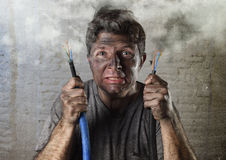 Untrained man joining electrical cable suffering electrical accident with dirty burnt face in funny shock expression Royalty Free Stock Images