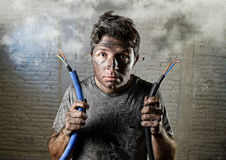 Untrained man joining electrical cable suffering electrical accident with dirty burnt face in funny shock expression stock images