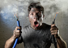 Untrained man joining electrical cable suffering electrical accident with dirty burnt face in funny shock expression. Young electrocuted man holding electrical Stock Photo