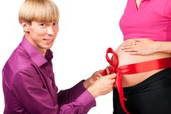 Untying red silk bow on stomach of pregnant woman Royalty Free Stock Photos