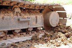 Ununterbrochene Bahnen der Nahaufnahme oder aufgespürtes Rad des Baggers oder des Löffelbaggers auf dem Bodenboden stockbild