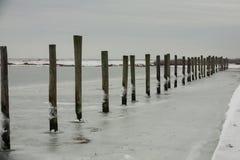 Ununterbrochene Linie von Dock-Stapel in gefrorenem Wasser Stockbild
