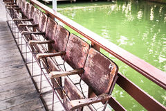Ununterbrochener hölzerner Stuhl außerhalb des thailändischen Hauses Stockfoto