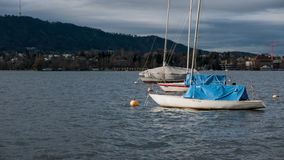 Unused boats on the Zurich lake in fall. A couple of boats ready for winter on the lake Stock Photography