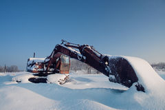 Unused excavator under  layer snow Royalty Free Stock Photography