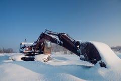 Unused excavator under  layer snow Royalty Free Stock Photography