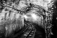 Unused mining tunnel with tracks. Old mining tunnel interior view with train tracks Stock Photos