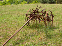 Unused and rusted farm plow in field. Rusted farm plow or plough pulled by horse in a field on farm Royalty Free Stock Photos