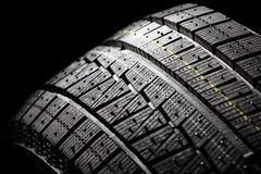 Unused winter car tire on a black background. Royalty Free Stock Photos