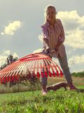 Unusual angle of woman raking leaves. Using rake. Person taking care of garden house yard grass. Agricultural, gardening equipment concept royalty free stock photography