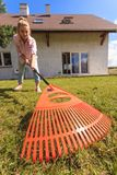 Unusual angle of woman raking leaves Royalty Free Stock Photography