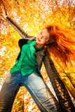 Unusual angle of young woman in autumn park Stock Photos