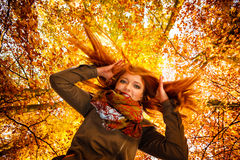 Unusual angle of young woman in autumn park Royalty Free Stock Photos
