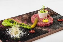 Unusual appetizer before main course on wooden board on white ba. Appetizer of meat patties raw minced meat with yolk eggs with sprouts on top and in white Stock Image