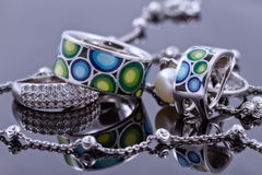 Unusual beautiful silver chain and a silver ring with gems. On the reflecting surface Stock Images