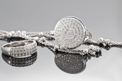 Unusual beautiful silver chain and a silver ring with gems. On the reflecting surface Stock Photo