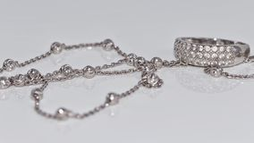 Unusual beautiful silver chain and a silver ring with gems. On the reflecting surface Stock Image
