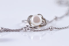 Unusual beautiful silver chain and a silver ring with pearl. On the reflecting surface Royalty Free Stock Images