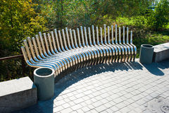 Unusual bench. Unusual metal pipe bench on pavement, summer day royalty free stock photography