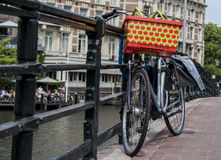 Unusual bicycle parked by canal in Amsterdam. Unusual bicycle with shopping basket chained by a canal in amsterdam Royalty Free Stock Photo