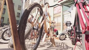 Unusual bicycles stand with other in line on street. Bicycle made of wooden boards. Sunny summer day. Unusual bicycles stand with other in line on street stock footage