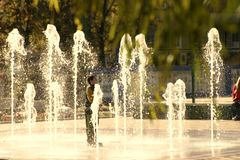 An unusual boy stands in the center of the fountain. royalty free stock photography