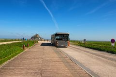 Unusual bus is going to the Mont Saint Michele abbey. Beautiful spring morning. Mont Saint-Michel, France-MAY 04, 2018: Unusual bus is going to the Mont Saint stock photography