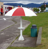 An unusual bus shelter in british columbia. A painted umbrella made of steel used for protection from the elements at prince rupert royalty free stock photos