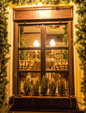 Unusual christmas wreath on window. Luxury decorated store front with garland lights in european city street at winter seasonal holidays stock images
