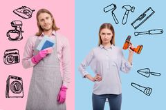 Unusual couple changing gender roles and looking satisfied with it. Interesting couple. Young woman standing for a gender equality and holding a drill while her royalty free stock photography